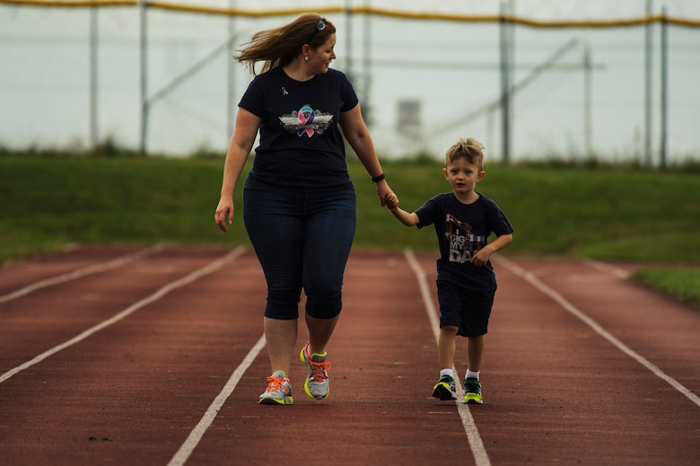 Jennifer Hartzog, cancer survivor, walks with her son Sam Hartzog during Relay For Life at Spangdahlem Air Base, Germany, July 29, 2016. Airmen and their families raised more than $12,000 for the American Cancer Society during this 24-hour relay event. (U.S. Air Force photo by Staff Sgt. Jonathan Snyder/Released)