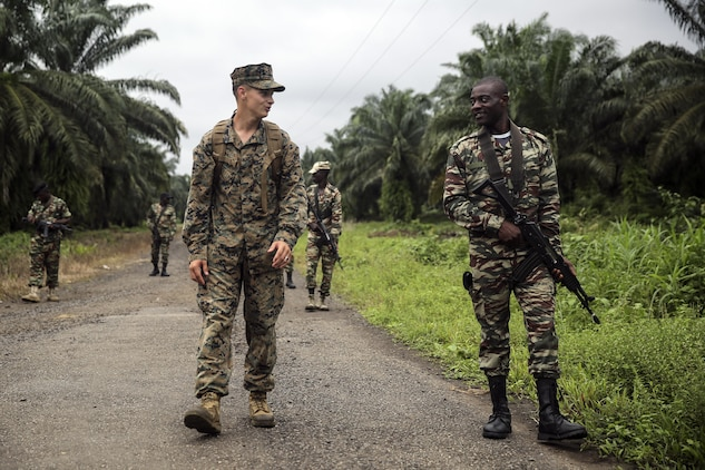 Cpl. Mitchell York, a rifleman with Special Purpose Marine Air-Ground Task Force Crisis Response-Africa, walks and talks with a Cameroonian soldier with Forces Fusiliers Marins et Palmeurs de Combat, during a patrolling exercise in Limbé, Cameroon, June 28, 2016.  Marines share tactics, techniques and skills with the FORFUMAPCO soldiers to combat the illicit trafficking in Cameroon.  (U.S. Marine Corps photo by Cpl. Alexander Mitchell/released)