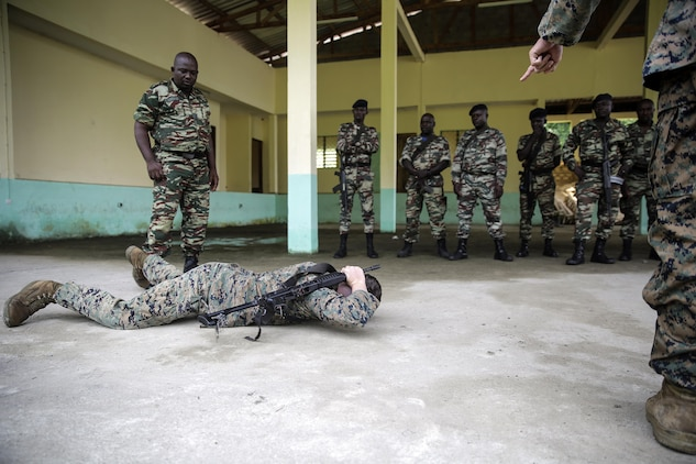 Lance Cpl. Dustin Kitts, a rifleman with Special Purpose Marine Air-Ground Task Force Crisis Response-Africa, shows a proper way to conduct a low crawl while maintaining safe control of the weapon for Cameroonian soldiers with Forces Fusiliers Marins et Palmeurs de Combat, in Limbé, Cameroon, June 28, 2016.  Marines share tactics, techniques and skills with the FORFUMAPCO soldiers to combat the illicit trafficking in Cameroon.  (U.S. Marine Corps photo by Cpl. Alexander Mitchell/released)