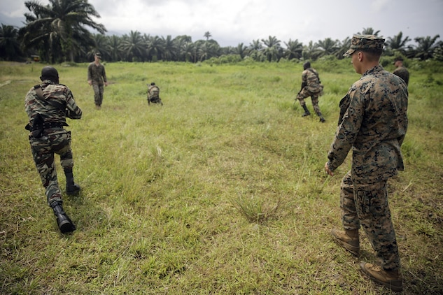 Cpl. Mitchell York, a rifleman with Special Purpose Marine Air-Ground Task Force Crisis Response-Africa, watches as Cameroonian soldiers with Forces Fusiliers Marins et Palmeurs de Combat, conduct buddy rushes in Limbé, Cameroon, June 28, 2016.  Marines share tactics, techniques and skills with the FORFUMAPCO soldiers to combat the illicit trafficking in Cameroon.  (U.S. Marine Corps photo by Cpl. Alexander Mitchell/released)