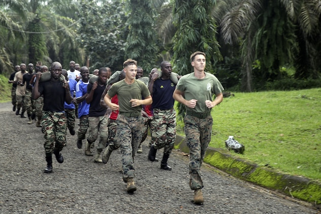 Two Marines with Special Purpose Marine Air-Ground Task Force Crisis Response-Africa, run with Cameroonian soldiers with Forces Fusiliers Marins et Palmeurs de Combat during a physical training exercise in Limbé, Cameroon, June 29, 2016.  Marines share tactics, techniques and skills with the FORFUMAPCO soldiers to combat the illicit trafficking in Cameroon.  (U.S. Marine Corps photo by Cpl. Alexander Mitchell/released)