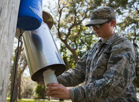 Airman Tayler Gottschalk, a 919th Special Operations Medical Squadron reservist, affixes a container to a trap near Post'l Point July 20 at Eglin Air Force Base, Fla. This permanently mounted trap is used to catch the general mosquito population. It is powered by electricity and runs for days to provide historical data. (U.S. Air Force photo/Ilka Cole)