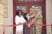 LEFT TO RIGHT: Shirley Avant-Ferguson, education services officer, Ken Steggemen, director of the Directorate of Human Resources, Brig. Gen. Patrick D. Frank, deputy commanding general for the 1st Infantry Division, and Col. John Lawrence, Fort Riley garrison commander, cut the ribbon to announce the official opening of Wainwright Hall July 18 following a rededication ceremony.