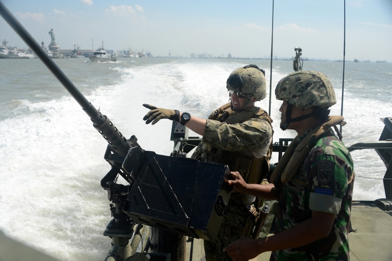 "In this file photo, Gunner's Mate 2nd Class Joseph Quartararo, assigned to Coastal Riverine Squadron (CRS) 3, speaks to an Indonesian ""Kopaska"" Naval Special Forces member while participating in a familiarization ride aboard a riverine command boat during Cooperation Afloat Readiness and Training (CARAT) Indonesia 2015. In its 21st year, CARAT is an annual, bilateral exercise series with the U.S. Navy, U.S. Marine Corps and the armed forces of nine partner nations including, Bangladesh, Brunei, Cambodia, Indonesia, Malaysia, the Philippines, Singapore, Thailand and Timor-Leste."