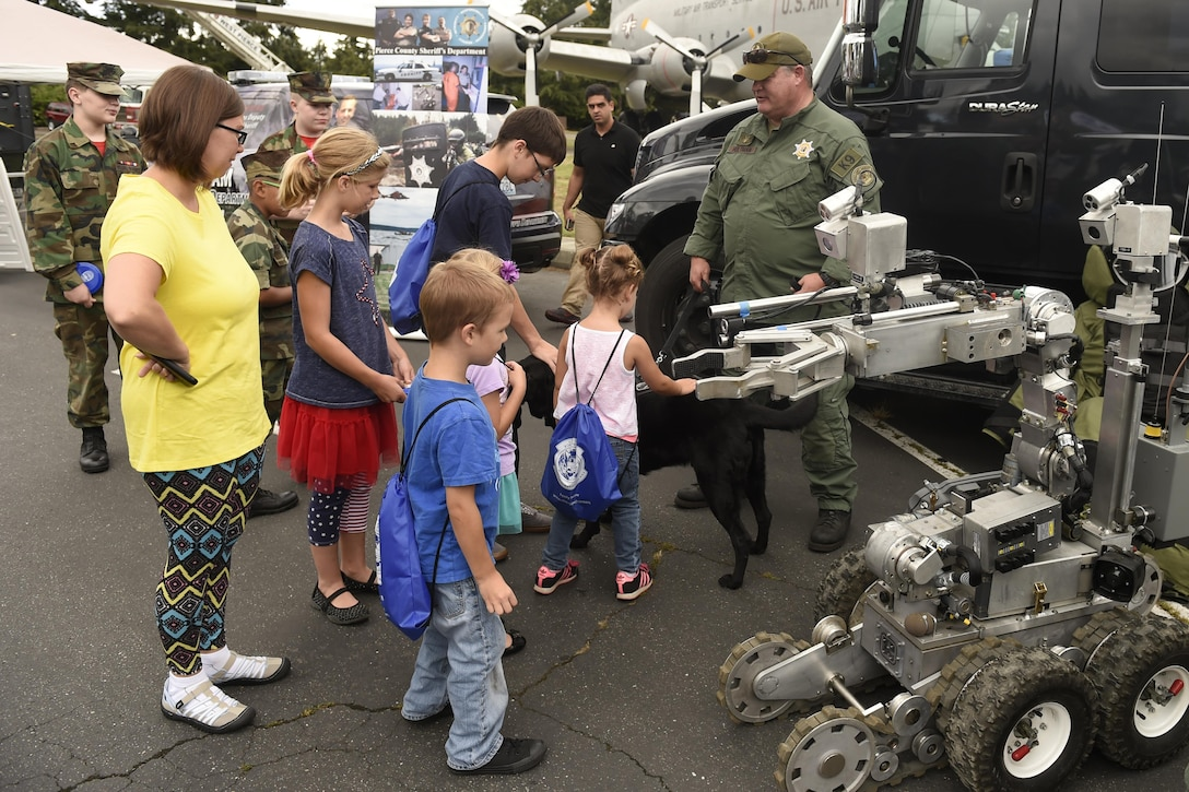 "Visitors at the ""Stand with Those Who Serve,"" annual public safety appreciation event talk with members of the Pierce County Sheriff's bomb squad July 23, 2016 at Joint Base Lewis-McChord, Wash. The event aimed to honor and bring together members of the area's first responder community. (U.S. Air Force photo/Tech. Sgt. Tim Chacon)"