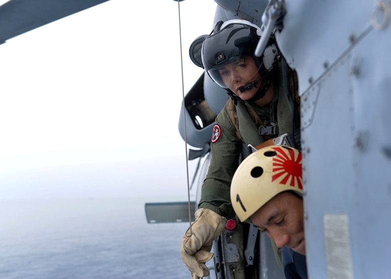 U.S. Navy Naval Aircrewman (Helicopter) 1st Class Calah Sanchez, top, assigned with the Helicopter Sea Combat Squadron 25, works with a Japanese Maritime Self-Defense Force member, bottom, during the Mine Countermeasures Exercise 2JA near the region surrounding Misawa Air Base, Japan, July 20, 2016. The annual bilateral exercise is held between the U.S. Navy and JMSDF to strengthen interoperability and increase proficiencies in mine countermeasure operations. (U.S. Navy photo by Mass Communication Specialist 2nd Class Samuel Weldin)