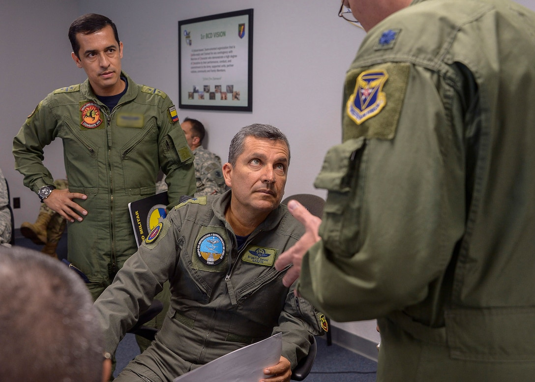 Colombian Air Force Brig. Gen. Sergio Andrés Garzón Vélez, Combined Forces Air Component Commander for PANAMAX 16, and his aid Lt. Col. Ricardo, receive an update during a commander's update briefing at Davis-Monthan AFB, Ariz., July 31, 2016.  PANAMAX is an annual exercise sponsored by U.S. Southern Command that increases the ability of nations to work together, enable assembled forces to organize as a multinational task force and test their responsiveness in combined operations. (U.S. Air Force photo by Tech. Sgt. Heather R. Redman)