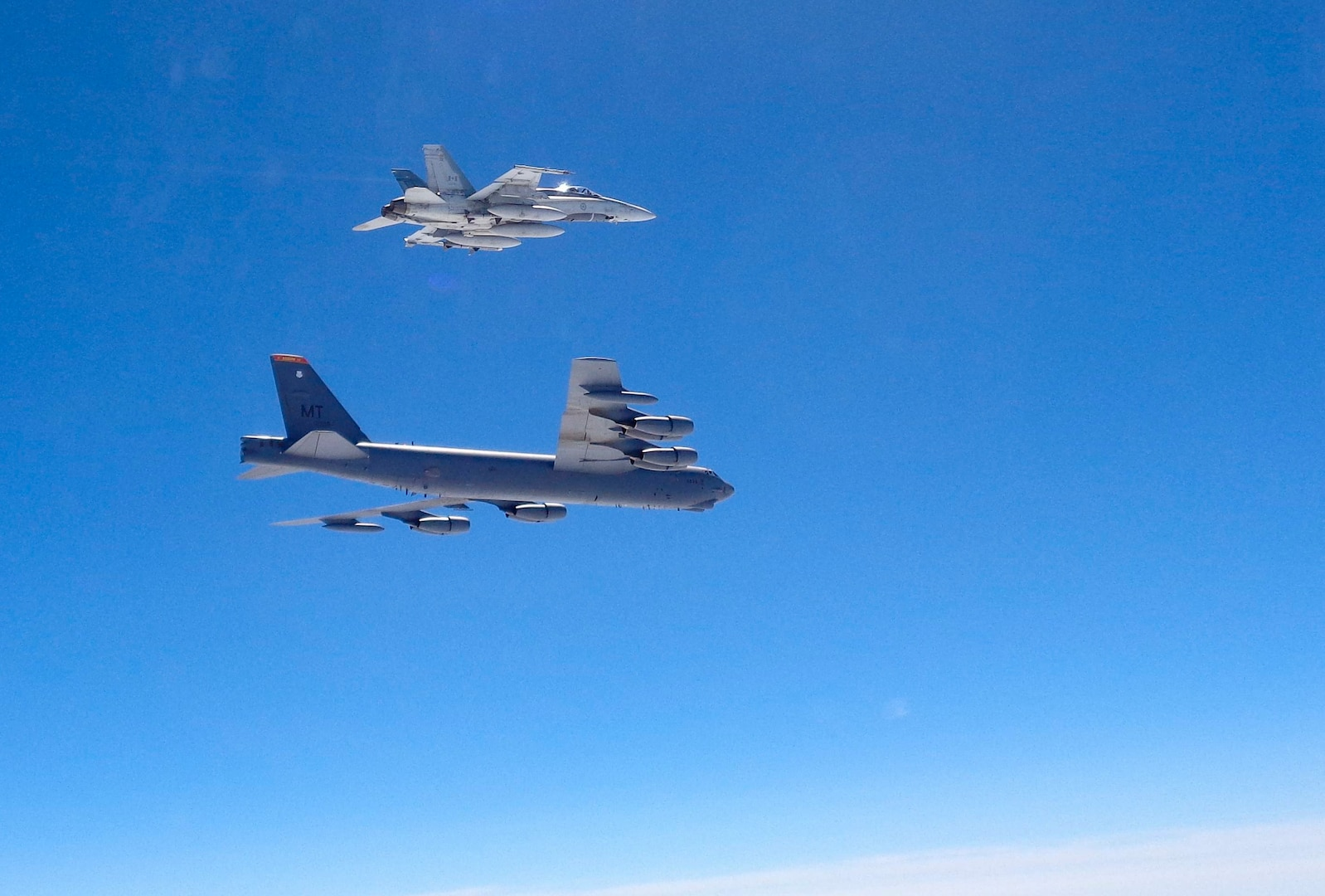 A Canadian CF-18 fighter jet intercepts a B-52 Stratofortress from the 2nd Bomb Wing, Barksdale Air Force Base, La., over the Atlantic in support of POLAR ROAR, Aug. 1, 2016. The B-52 flew non-stop from the U.S. to the Baltic Sea and back to conduct the intercept training with NORAD-assigned Canadian fighter aircraft and NATO allies. In total, three B-52s and two B-2 Spirit bombers from all three of the U.S.'s strategic bomber bases (Barksdale AFB, La.; Minot AFB, N.D.; and Whiteman AFB, Mo.) participated in POLAR ROAR, which also included flights to the Arctic and Alaska's Aleutian Islands.  Strategic bomber missions like POLAR ROAR ensure crews maintain the readiness and proficiency necessary to provide an always-ready global strike capability. (Photo courtesy of Canadian NORAD Region)