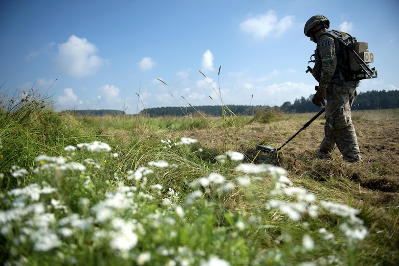 U.S. Air Force Tech. Sgt. Ryan Tennyson, 52nd Civil Engineer Squadron explosive ordnance disposal team leader, scans a field with a metal detector during an Improvised Explosive Device Rodeo at Spangdahlem Air Base, Germany, July 27, 2016. The exercise, known as the IED Rodeo, represented the first of its kind at Spangdahlem and featured a multilateral event showcasing EOD members from different branches and nations, how they locate explosive devices and the steps they take to safely and effectively disarm them. (U.S. Air Force photo by Airman 1st Class Preston L. Cherry/Realeased)