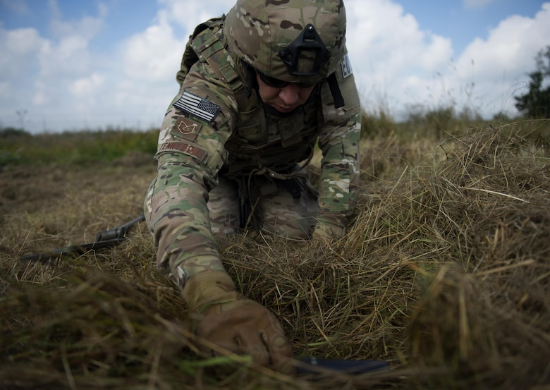U.S. Air Force Tech. Sgt. Ryan Tennyson, explosive ordnance disposal team leader, uses a metal detecting wand to scan an area for simulated improvised explosive devices at Spangdahlem Air Base, Germany, July 27, 2016. This multilateral exercise focused on locating and disarming improvised explosive devices which involved EOD members from the U.S., Czech Republic, Germany and Belgium. (U.S. Air Force photo by Airman 1st Class Preston L. Cherry/Realeased)