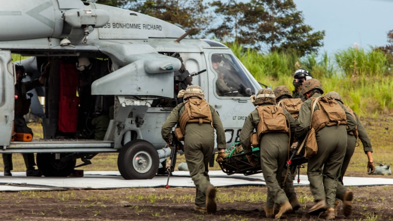 Expeditionary fire rescue Marines with Marine Wing Support Squadron 171 stationed at Marine Corps Air Station Iwakuni, Japan, carry a simulated casualty to a Sikorsky MH-60S Seahawk with Helicopter Sea Combat Squadron 25 during Exercise Eagle Wrath 2016 at Combined Arms Training Center Camp Fuji,Japan, July 28, 2016. During the culminating event Marines established a mock air base including a landing zone and refueling point, constructed defensive and machine-gun positions, and conducted convoys and patrols over the course of four days.
