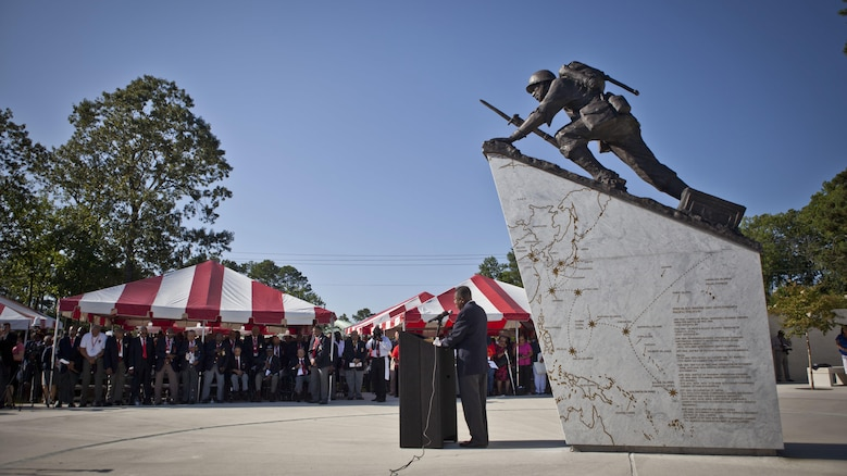 U.S. service members and guests listen to the National Chaplain of the Montford Point Marine Association,  Reverend James E. Moore, as he delivers the invocation during the Montford Point Marine Memorial dedication ceremony held at Jacksonville, North Carolina, July 29, 2016. The memorial was built in honor of the 20,000 African-Americans who attended training at Montford Point.