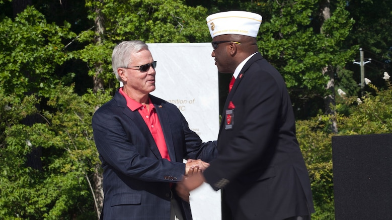 General (Ret) James F. Amos, left, 35th Commandant of the Marine Corps, and Forest E. Spencer, National President of the Montford Point Marine Association, greet each other during the Montford Point Marine Memorial dedication ceremony held at Jacksonville, North Carolina, July 29, 2016. The memorial was built in honor of the 20,000 African-Americans who attended training at Montford Point.