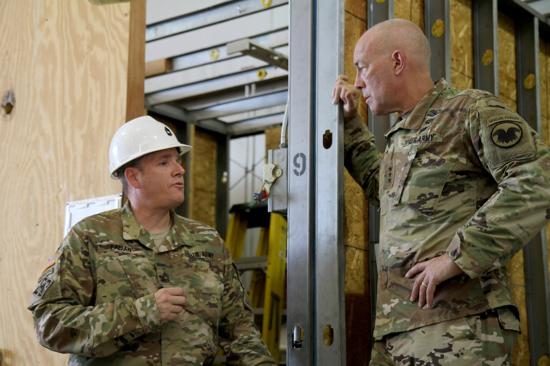 Master Sgt. Christopher Fabian, course manager for Tactical Training Center Dix, gives Lieutenant General Charles D. Luckey, commanding general of the U.S. Army Reserve, a brief run-down of his classroom's capabilities, including the training booth which allows students to gain practical experience in everything from basic plumbing to electrical wiring installation. Luckey met with more than a dozen students and instructors from the second phase of the 80th Training Command's carpentry and masonry specialist course during during Luckey's visit to Fort Dix, N.J. July 16, 2016.