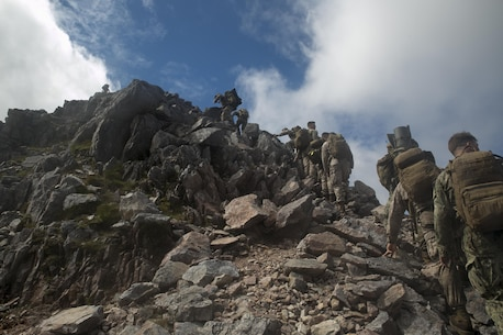 U.S. Marines, sailors and Royal Commandos climb to the summit of a mountain, July 20, 2016, in the Scottish Highlands, Inverness, Scotland, during the mountain training phase of the Tartan Eagle 16 exercise. The mountain training phase consisted of learning mountain survival skills, map reading and how to successfully traverse a mountain. Tartan Eagle is an annual training event that began in 1994. Marines and sailors with Marine Corps Security Force Regiment trained alongside 43 Command Fleet Protection Group Royal Commandos to exchange best security and training practices and to foster good relations between the two commands. The exercise allowed for the exchange of tactics, techniques and procedures in the security of strategic assets. (Official Marine Corps photo by Sgt. Calvin Shamoon/ Released)