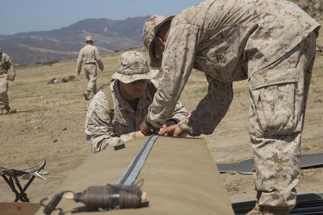 Cpl. Ryan T. Fry and Lance Cpl. Fabian J. Villegas, combat engineers with 1st Battalion, 5th Marine Regiment, 1st Marine Division, assemble a linear breaching charge with detonation cord at Camp Pendleton, Calif., July 26, 2016. A live-fire training exercise was conducted to give assaultmen and riflemen an opportunity to integrate with combat engineers and learn to build improvised breaching charges. (U.S. Marine Corps Photo by Lance Cpl. Bradley J. Morrow)