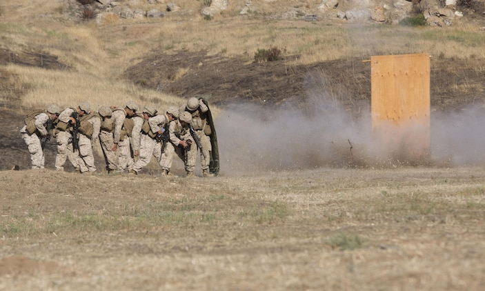 Marines from 1st Battalion, 5th Marine Regiment, 1st Marine Division shield themselves behind a blast blanket as they detonate a water charge at Camp Pendleton, Calif., July 26, 2016. Marines from the battalion conducted a live-fire exercise to create a realistic training environment and familiarize them with improvised breaching charges. (U.S. Marine Corps Photo by Lance Cpl. Bradley J. Morrow)