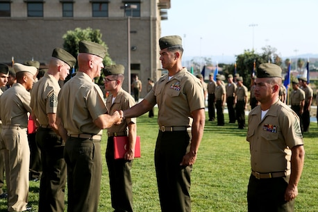 U.S. Marine Brig. Gen. David A. Ottignon greets and presents the Marine Corps Engineer Association Award to Capt. Juan Rodriguez at the 1st Marine Logistics Group quarterly awards ceremony aboard Camp Pendleton Calif., July 29, 2016. Ottignon is the 1st MLG commanding general and Rodriguez is the executive officer of 1st Explosive Ordnance Disposal Company, 7th Engineer Support Battalion. Rodriguez was one of the Marines recognized at the ceremony for their outstanding achievements in the performance of their duties for the fiscal year 2016 third quarter. (U.S. Marine Corps photo by Sgt. Carson Gramley/released)