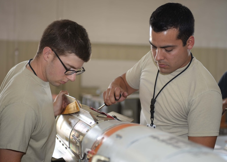 Airman 1st Class Forrest Roach, a conventional maintenance crewmember, left, works with Staff Sgt. Anthony Anderson, a conventional maintenance crew chief and munitions inspector, both assigned to the 28th Munitions Squadron, to attach a fin to an MK 62 mine at Ellsworth Air Force Base (AFB), S.D., July 20, 2016. Due to his grandfather and fathers' service in the branch, Anderson was inspired to join the Air Force in September 2008, and hopes to stay in as long as he is able to. (U.S. Air Force photo by Airman 1st Class Sadie Colbert)