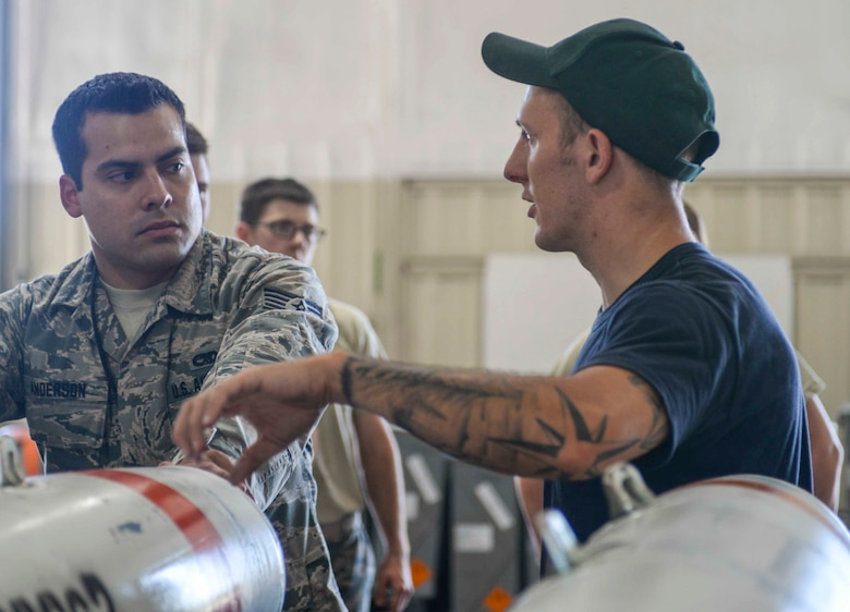 Staff Sgt. Anthony Anderson, a conventional maintenance crew chief and munitions inspector assigned to the 28th Munitions Squadron, receives direction from Petty Officer Second Class Nick Werner, a minesman assigned to the Navy Munitions Command (NMC) Atlantic Unit, Charleston, S.C., at Ellsworth Air Force Base (AFB), S.D., July 20, 2016. Sailors from the NMC Unit Charleston were sent to Ellsworth to train Airmen on building mines for the B-1 bomber to deploy. (U.S. Air Force photo by Airman 1st Class Sadie Colbert)