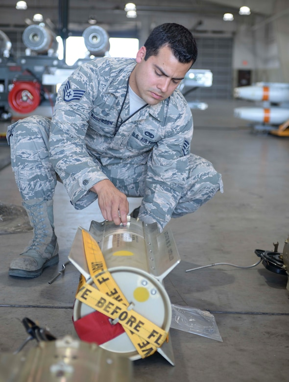 Staff Sgt. Anthony Anderson, a conventional maintenance crew chief and munitions inspector assigned to the 28th Munitions Squadron, works to connect a lanyard to a pin connected to the bomb tail at Ellsworth Air Force Base (AFB), S.D., July 20, 2016. Anderson said one of the many things that keeps him motivated is seeing his work pay off downrange and encourages Airmen to always have a positive attitude. (U.S. Air Force photo by Airman 1st Class Sadie Colbert)
