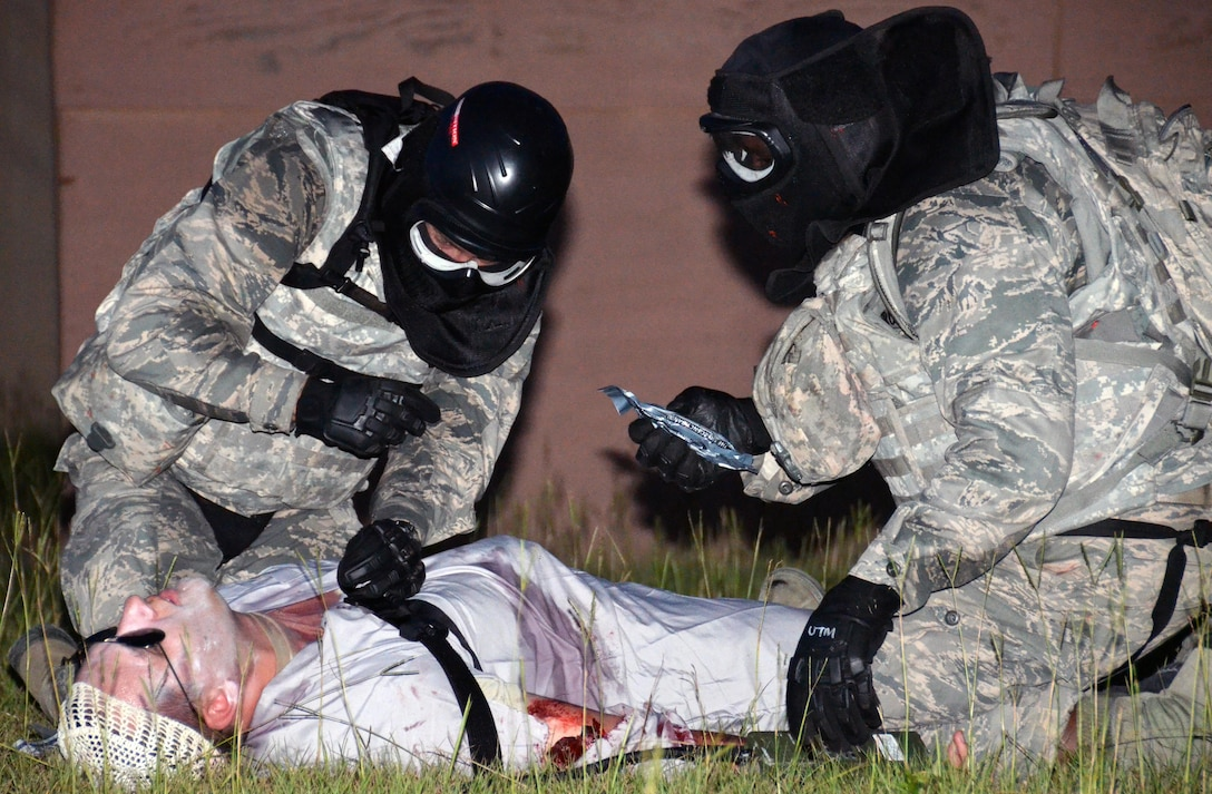 Two chaplain candidates render self-aid buddy care to a casualty during a field exercise at Robins Air Force Base, Georgia, July 27, 2016. The candidates are participating in the Air Force Reserve Command Chaplain Candidate Intensive Interview program which aims to provide an extensive overview of what the Air Force Reserve mission is as well as a broad overview of the military chaplain corps. During the last week of the program, the candidates were immersed in fast-paced mobility training conducted by active-duty instructors from the 5th Combat Communications Squadron Support. (U.S. Air Force photo/Tech. Sgt. Kelly Goonan)