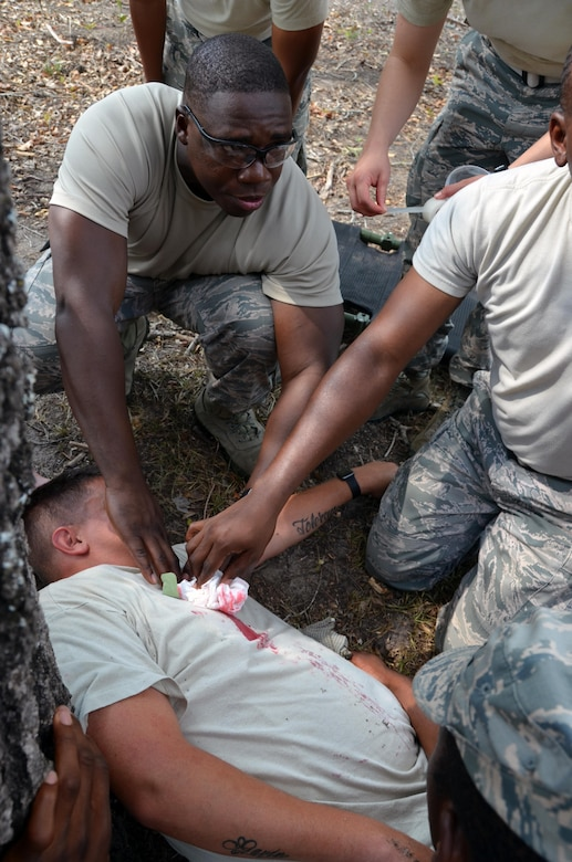 "2nd Lieutenant Willy Gedeon, Chaplain Candidate, provides self-aid buddy care by holding pressure on an open wound during a training scenario with ""wounded"" civilians at Robins Air Force Base, Georgia, July 25. The candidates are participants in the Air Force Reserve Command Chaplain Candidate Intensive Interview program which aims to provide an extensive overview of the Air Force Reserve mission and military chaplain corps.(U.S. Air Force photo/Tech. Sgt. Kelly Goonan)"