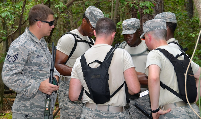 Staff Sgt. Robert Oberle, 5th Comabat Communications Squadron Support, observes his group of five chaplain candidates as they use their land navigation training to plot points onto a map to get to their specified location at Robins Air Force Base, Ga, July 25. The candidates are participants in the Air Force Reserve Command Chaplain Candidate Intensive Interview program which aims to provide an extensive overview of what the Air Force Reserve mission is as well as a broad overview of the military chaplain corps.(U.S. Air Force photo/Tech. Sgt. Kelly Goonan)