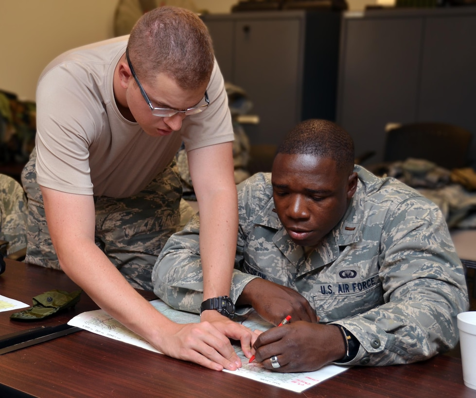 2nd Lieutenant Nathaniel Cantu helps 2nd Lieutenant Willy Gedeon figure out how to plot coordinates onto a map at Robins Air Force Base, Georgia, July 25, 2016. The candidates are participating in the Air Force Reserve Command Chaplain Candidate Intensive Interview program which aims to provide an extensive overview of what the Air Force Reserve mission is as well as a broad overview of the military chaplain corps. During the last week of the program, the candidates were immersed in fast-paced mobility training conducted by active-duty instructors from the 5th Combat Communications Squadron Support. (U.S. Air Force photo/Tech. Sgt. Kelly Goonan)