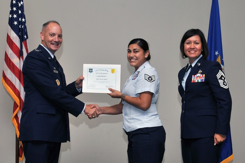 U.S. Air Force Col. Michael Downs, 17th Training Wing Commander, and Chief Master Sgt. JoAnne Bass, 17th Training Wing Command Chief, present the NCO of the Quarter award to Staff Sgt. Erica James, 17th Communications Squadron, during the wing quarterly awards ceremony at the Event Center on Goodfellow Air Force Base, Texas, July 29, 2016. (U.S. Air Force photo by Staff Sgt. Laura R. McFarlane/Released)