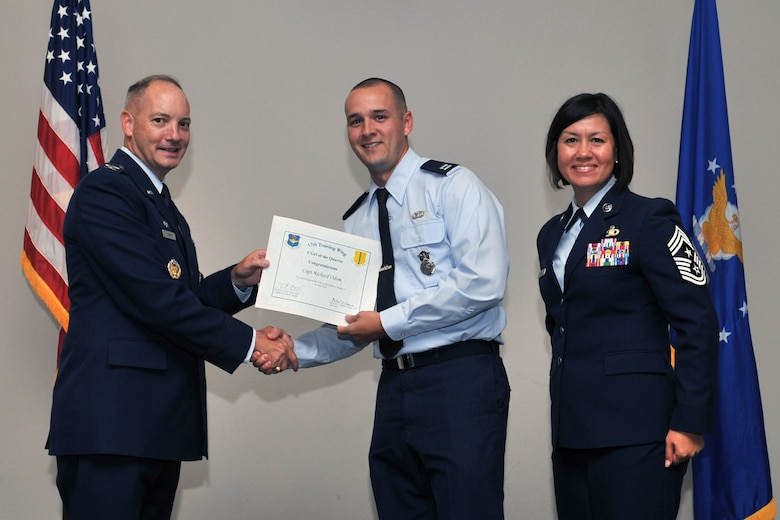 U.S. Air Force Col. Michael Downs, 17th Training Wing Commander, and Chief Master Sgt. JoAnne Bass, 17th Training Wing Command Chief, present the Company Grade Officer of the Quarter award to Capt. Richard Odom, 17th Security Forces Squadron, during the wing quarterly awards ceremony at the Event Center on Goodfellow Air Force Base, Texas, July 29, 2016. (U.S. Air Force photo by Staff Sgt. Laura R. McFarlane/Released)