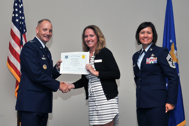 U.S. Air Force Col. Michael Downs, 17th Training Wing Commander, and Chief Master Sgt. JoAnne Bass, 17th Training Wing Command Chief, present the 17th Training Wing Civilian Category I Supervisory of the Quarter award to Brittany Furr, 17th Force Support Squadron, during the wing quarterly awards ceremony at the Event Center on Goodfellow Air Force Base, Texas, July 29, 2016. (U.S. Air Force photo by Staff Sgt. Laura R. McFarlane/Released)
