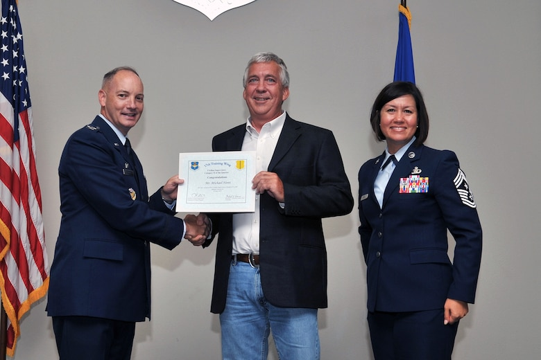 U.S. Air Force Col. Michael Downs, 17th Training Wing Commander, and Chief Master Sgt. JoAnne Bass, 17th Training Wing Command Chief, present the 17th Training Wing Civilian Category II Supervisory of the Quarter award to Michael Noret, 17th Civil Engineer Squadron, during the wing quarterly awards ceremony at the Event Center on Goodfellow Air Force Base, Texas, July 29, 2016. (U.S. Air Force photo by Staff Sgt. Laura R. McFarlane/Released)