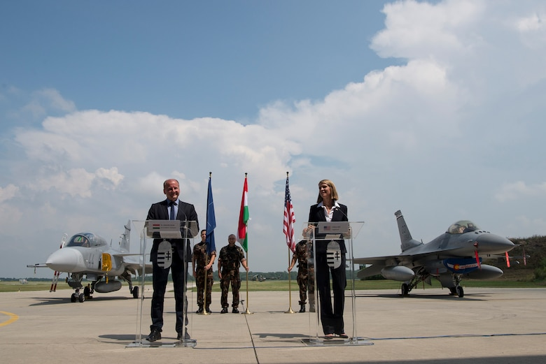 Dr. Simicsko Istvan, Hungarian Minister of Defense and Colleen Bell, U.S. Ambassador to Hungary, speak to American and Hungarian troops at Pápa Air Base, Hungary during Panther Strike 2016, July 27, 2016. A Hungarian Gripen and an American F-16 were both used during the multinational training event and can be seen in the background. Istvan and Bell were amongst the senior officials in attendance for distinguished visitor day, all of whom received an opportunity to tour the base, speak with individuals participating in the training mission and and see the aircraft involved. (U.S. Air National Guard photo by Senior Master Sgt. John Rohrer)