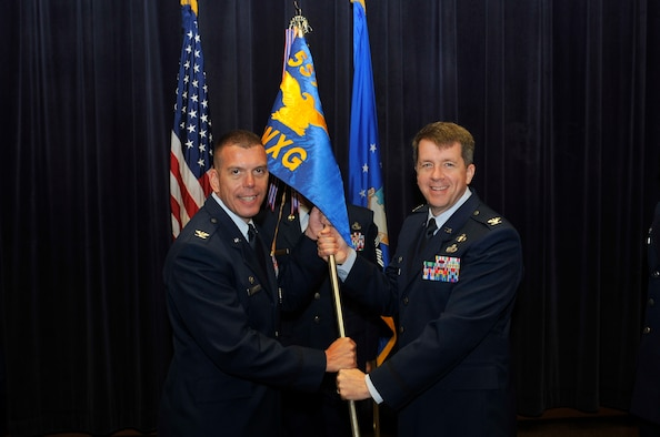 Col. Steven Dickerson, commander of the 557th Weather Wing, left, receives the guidon from Col. Donald Shannon, the outgoing commander of the 2nd Weather Group in the 557th WW Auditorium at Offutt Air Force Base, Neb., Aug. 1, 2016. Shannon passed command to Col. Jason Patla. (U.S. Air Force photo/Jeff Bridges)