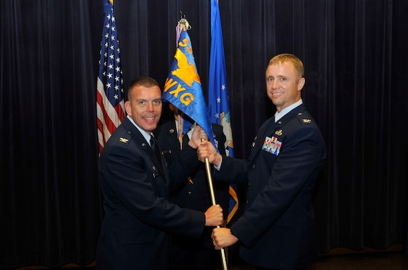 Col. Steven Dickerson, commander of the 557th Weather Wing, left, passes the guidon to Col. Jason Patla, the incoming commander of the 2nd Weather Group in the 557th WW Auditorium at Offutt Air Force Base, Neb., Aug. 1, 2016. Patla assumed command from Col. Steven Shannon, who served as commander for the last two years. (U.S. Air Force photo/Jeff Bridges)