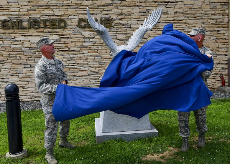 Col. Andrew Hansen, 51st Fighter Wing commander, and Chief Master Sgt. Alex Del Valle, 51st Fighter Wing command chief, unveil the new eagle statue dedicated to retired Master Sgt. Jim Price outside of the base enlisted club at Osan Air Base, Republic of Korea, Aug. 1, 2016. The previous eagle statue was damaged in the fall of 2015, and was replaced with a larger, more detailed statue thanks largely to the efforts and contributions of the Osan Chief's Group, Team Osan Spouses Club, and the 731st Air Mobility Squadron. (U.S. Air Force photo by Senior Airman Victor J. Caputo/Released)