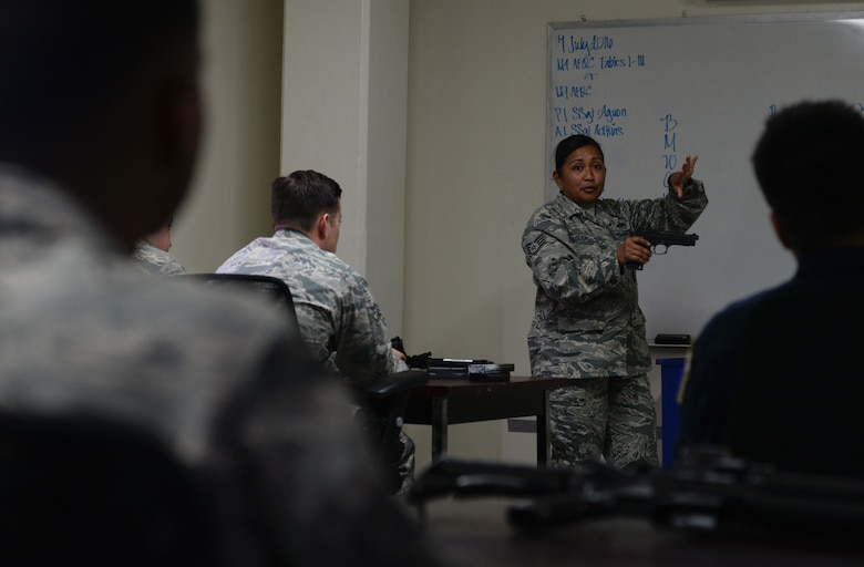 Staff Sgt. Lolita Aguon, 36th Security Forces Squadron combat arms instructor, demonstrates safe and effective use of the M9 pistol July 7, 2016, at Andersen Air Force Base, Guam. Andersen's combat arms team trains service members and civilians from many Department of Defense organizations on safe and effective use of firearms. (U.S. Air Force photo by Airman 1st Class Jacob Skovo)
