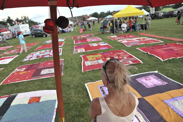 An umbrella station held speakers that let visitors listen to stories from survivors throughout the night as they sit in the middle of Monument Quilt squares during National Night Out August 2, 2016 at Fort George G. Meade, Md. The Monument Quilt is an ongoing collection of stories and message from survivors of sexual and domestic violence, the stories are written then stitched onto red quilt squares which will have 6,000 quilts displayed at the National Mall in 2018. (U.S. Air Force photo/Staff Sgt. Alexandre Montes)