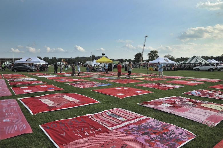 Pieces of the Monument Quilt lay on the parade field during National Night Out August 2, 2016 at Fort George G. Meade, Md. The Monument Quilt is an ongoing collection of stories and message from survivors of sexual and domestic violence, the stories are written then stitched onto red quilt squares which will have 7,000 quilts displayed at the National Mall in 2018. (U.S. Air Force photo/Staff Sgt. Alexandre Montes)