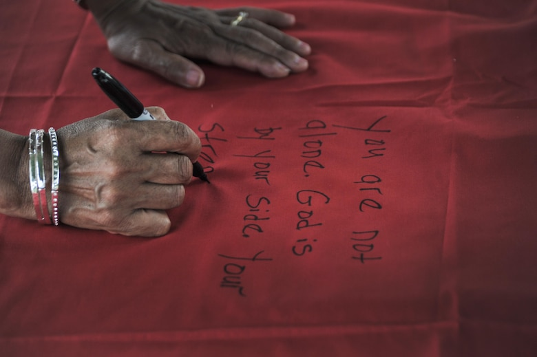 Participants were given the chance to write messages as supporters or survivors of rape or abuse on pieces that will be stitched onto the Monument Quilt during National Night Out August 2, 2016 at Fort George G. Meade, Md. The Monument Quilt is an ongoing collection of stories and message from survivors of sexual and domestic violence, the stories are written then stitched onto red quilt squares which will have 6,000 quilts displayed at the National Mall in 2018.  (U.S. Air Force photo/Staff Sgt. Alexandre Montes)