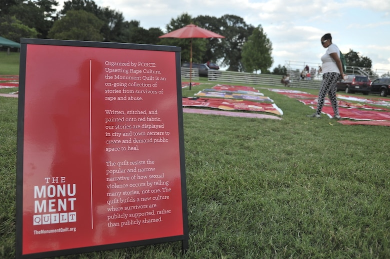Pieces of the Monument Quilt lay on the parade field during National Night Out August 2, 2016 at Fort George G. Meade, Md. The Monument Quilt is an ongoing collection of stories and message from survivors of sexual and domestic violence, the stories are written then stitched onto red quilt squares which will have 6,000 quilts displayed at the National Mall in 2018. (U.S. Air Force photo/Staff Sgt. Alexandre Montes)