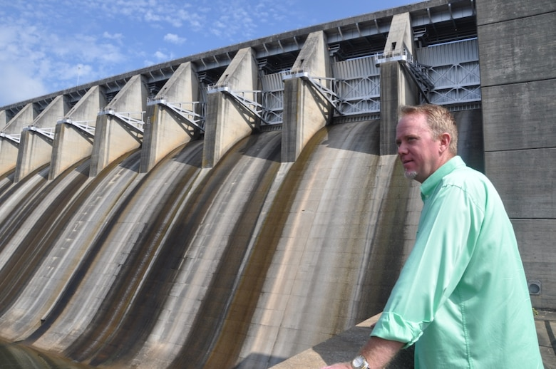 Operator Trainee Les Rice poses before Thurmond Dam's spillway gates July 6. Rice is a 4th-year operator trainee in the Savannah District's Operator Training Program. The competitive program accepts only an elite crop of qualified candidates who must endure 4-5 years of demanding requirements surrounding dam operations.
