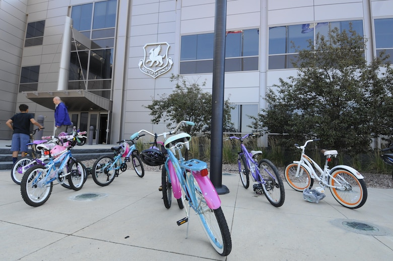 Children's bicycles line the front of Building 210 at Schriever Air Force Base, Colorado, before the Amazing gRace: Kids Edition Saturday, July 30, 2016. Competitors were required to ride bicycles during the scavenger hunt to reach the stations scattered throughout the base. (U.S. Air Force photo/2nd Lt. Darren Domingo)