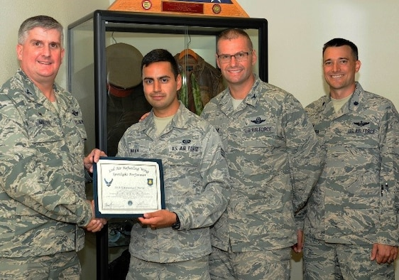 Senior Airman Emmanuel Nava, 22nd Operations Support Squadron intelligence standards and evaluations journeyman, poses with Col. Albert Miller, 22nd Air Refueling Wing commander, Col. Phil Hesseltine, 22nd ARW vice commander, and Lt. Col. Walenga, 22nd OSS commander, July 19, 2016, at McConnell Air Force Base, Kan. Nava received the spotlight performer for the week of June 6-10. (U.S. Air Force photo/Senior Airman David Bernal Del Agua)