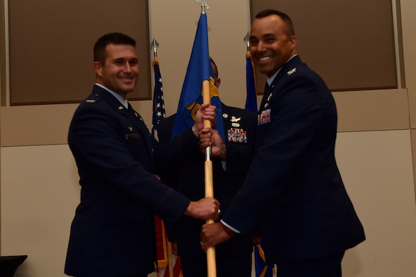 Col. Lorenzo Bradley, 460th Operations Group commander, assumes command August 2, 2016, during the OG assumption of command ceremony at the Leadership Development Center on Buckley Air Force Base, Colo. The guidon is exchanged during the ceremony as a symbol providing a view of the command authority being transferred from one commander to the next. (U.S. Air Force photo by Airman 1st Class Gabrielle Spradling/Released)