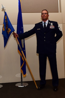Chief Master Sgt. Joseph Stratil, 460th Operations Group superintendent, guards the OG guidon August 2, 2016, during the OG assumption of command ceremony at the Leadership Development Center on Buckley Air Force Base, Colo. The guidon is exchanged during the ceremony as a symbol providing a view of the command authority being transferred from one commander to the next. (U.S. Air Force photo by Airman 1st Class Gabrielle Spradling/Released)