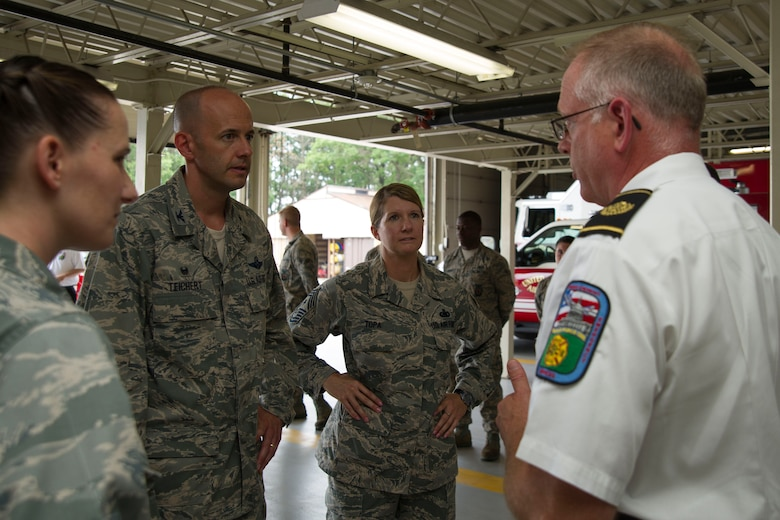 "Col. John Teichert, 11th Wing and Joint Base Andrews commander, and Chief Master Sgt. Beth Topa, 11th WG command chief master sergeant, talk with Timothy Pitman, 11th Civil Engineer Squadron fire chief, at Fire Station One at JBA, Md., Aug. 1, 2016. Teichert visited several of the 11th Mission Support Group squadrons with Chief Master Sgt. Beth Topa, 11th WG command chief master sergeant, to become more familiar with the squadrons' missions and meet with ""America's Airmen."" (U.S. Air Force photo by Airman 1st Class Rustie Kramer)"