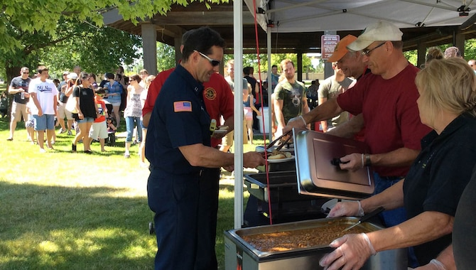 Airmen and their families line up to get BBQ smoked brisket, ribs, pulled pork, baked beans and slaw at the Military Appreciation BBQ on July 30, 2016, at Miller Park, Fairchild Air Force Base, Wash. The event was sponsored by Uncle Leroy & the Pit Masters, a local retailer at Spokane Public Market that provided the food to people at the base for free in appreciation of their service and sacrifice.