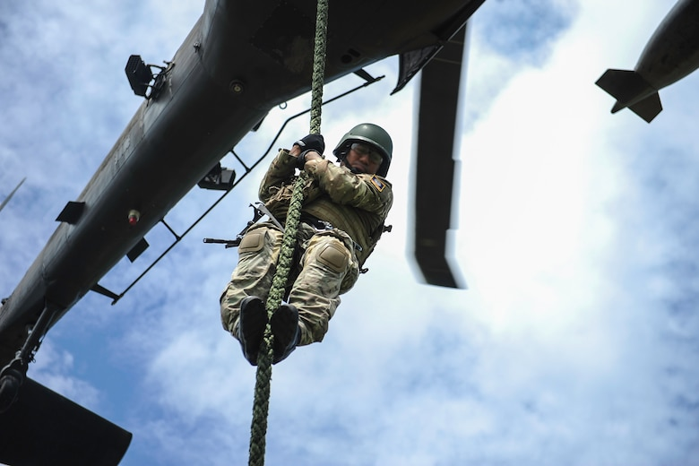A member of the Belize Special Assignment Group fast ropes out of a UH-60 Black Hawk assigned to Joint Task Force-Bravo's 1st Battalion, 228th Aviation Regiment during training at Price Barracks, Belize, July 19, 2016. For many of the BSAG participants, this was their first time they were part of Fast Rope Insertion and Extraction System (FRIES) training. (U.S. Air Force photo illustration by Staff Sgt. Siuta B. Ika)